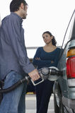 Couple Pumping Gas Into Car Stock Image