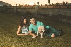 Couple with a puppy dog in the countryside. Man and woman with their adorable puppy in a sunset. stock photo