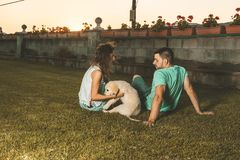 Couple with a puppy dog in the countryside. Man and woman with their adorable puppy in a sunset. royalty free stock photo