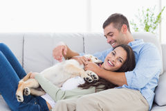 Couple with puppy relaxing on sofa Royalty Free Stock Photography