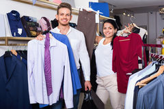 Couple purchasing clothes for two in boutique Stock Photos
