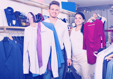 Couple purchasing clothes for two in boutique Stock Images
