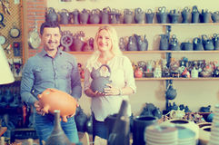 Couple purchasing kitchenware. Portrait of smilling couple purchasing clay kitchenware royalty free stock photos