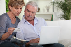 Couple purchasing over the  internet. A mature couple purchasing goods over the internet Stock Images