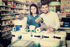 Couple purchasing tools for house improvements in paint supplies Royalty Free Stock Photo