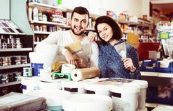 Couple purchasing tools for house improvements in paint supplies. Smiling happy cheerful couple purchasing tools for house improvements in paint supplies store royalty free stock images