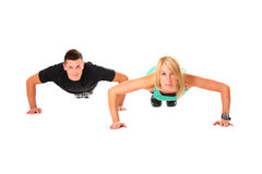 Couple push-ups. A picture of a young couple doing push-ups over white background stock photo