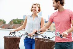 Couple Pushing Bikes With City Skyline In Background Stock Image