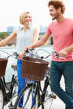 Couple Pushing Bikes With City Skyline In Background Royalty Free Stock Photo
