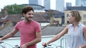 Couple Pushing Bikes With City Skyline In Background. Young couple pushing bikes towards camera with urban skyline in background.Shot on Sony FS700 in PAL format stock video
