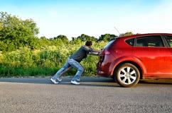 Couple pushing a broken car Stock Photo