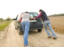 Couple pushing a car Stock Photography
