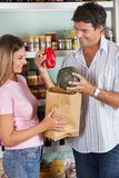 Couple Putting Bellpepper And Pumpkin In Paper Bag Royalty Free Stock Photo
