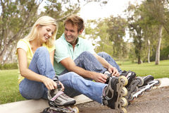 Couple Putting On In Line Skates In Park Royalty Free Stock Images