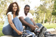 Couple Putting On In Line Skates In Park royalty free stock photography