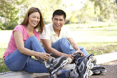 Couple Putting On In Line Skates In Park Stock Photo