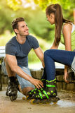 Couple putting on in line skates in park Stock Images