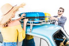 Couple putting luggage on car roof. Cheerful young couple of travelers putting luggage on car roof isolated on white Stock Photography