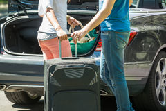 Couple Putting Luggage In A Car Trunk. Close-up Of Couple Putting Luggage In A Car Trunk Royalty Free Stock Photo