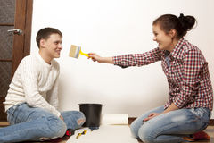 Couple putting new wallpaper Stock Image