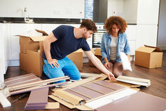 Couple Putting Together Self Assembly Furniture In New Home. Reading Instructions stock image
