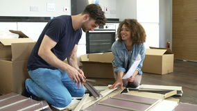 Couple Putting Together Self Assembly Furniture In New Home Stock Footage