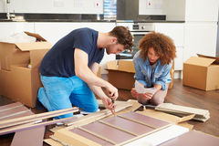 Couple Putting Together Self Assembly Furniture In New Home. Whilst Reading Instructions Royalty Free Stock Image