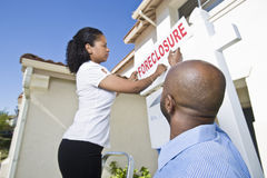 Couple putting up notice outside house Stock Photography
