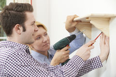 Couple Putting Up Wooden Shelf Together At Home Stock Images