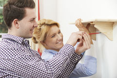 Couple Putting Up Wooden Shelf Together At Home Stock Photography