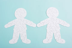 Couple puzzle of relationships. A puzzle in shape of a two human people - the puzzle of relationships - on blue background Royalty Free Stock Photo