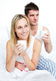 Couple in pyjamas drinking coffee in bed Stock Images
