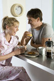 Couple in pyjamas sitting at breakfast bar in kitchen, holding mug and glass, laughing, side view Stock Photography