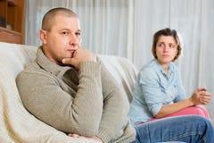 Couple quarrel at home. Sad ordinary men against unhappy woman Stock Photos