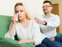 Couple after quarrel. Man asking for forgiveness from sad women after quarrel at home. Focus on girl Stock Photos