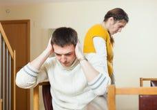 Couple quarrel. Sad  men listening to women at home Stock Photo