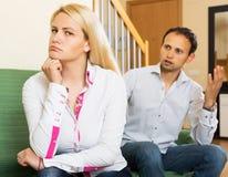 Couple quarrel. Upset ordinary men against unhappy women  at home Stock Photography