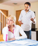 Couple quarrel. Upset ordinary men against unhappy women in living room at home Stock Photography