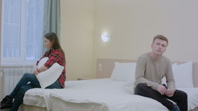 Couple quarreling sitting on bed in bedroom at home. Professional shot in 4K resolution. 068. You can use it e.g. in your commercial video, business, travel stock footage