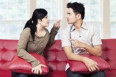 Couple quarreling while sitting on sofa Royalty Free Stock Photos