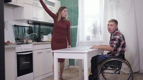 Couple of quarrels, disabled person in a wheelchair scandalously swears with his aggressive wife and shout at each other