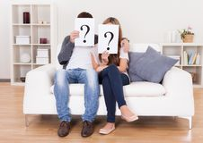 Couple with question marks Royalty Free Stock Photos