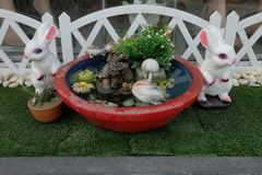 Couple rabbits, duck and turtles in mini mock garden. Stock Photo