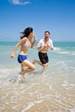 Couple racing on the beach wit Royalty Free Stock Photo