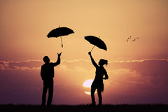 Couple in the rain at sunset Stock Image