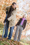 Couple raking up autumn leaves Royalty Free Stock Photo