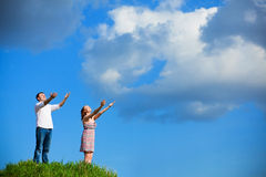 Couple reach out to sun. On top of hill stock photography