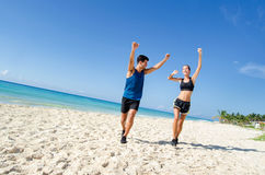 Couple reaching goal at the beach. Young couple reaching goal at the beach. Fitness Stock Photography