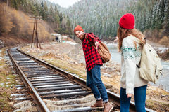 Couple reaching hands and waking on railroad in mountains Royalty Free Stock Photo