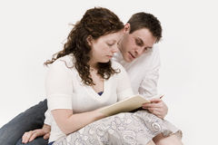 Couple reading. A beautiful young couple a book reading together royalty free stock photography